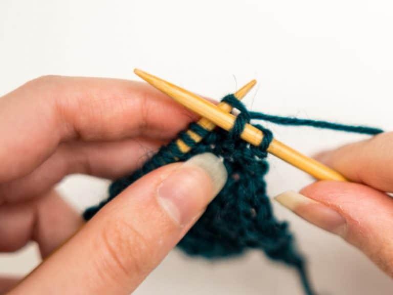 mains qui tricotent de la laine verte
