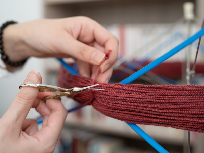 ciseau qui coupe de la laine rouge