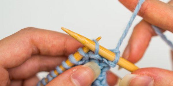 mains qui tricote de la laine bleu